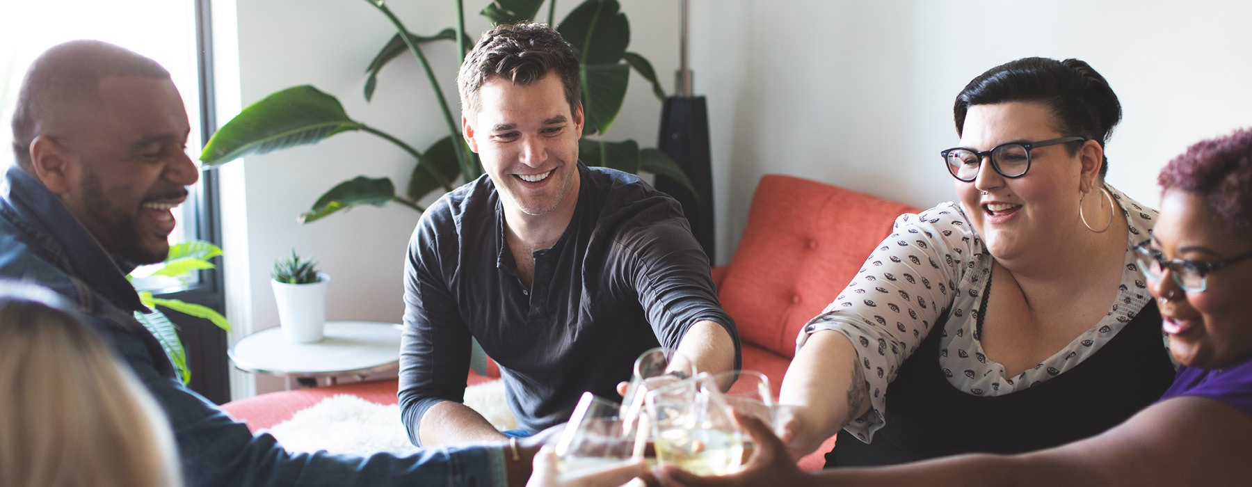 friends clink glasses in bright living room